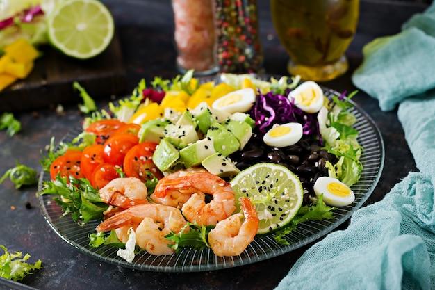 Gezonde saladeplaat. vers zeevruchtenrecept. gegrilde garnalen en verse groentesalade - avocado, tomaat, zwarte bonen, rode kool en paprika. gegrilde garnalen. gezond eten.