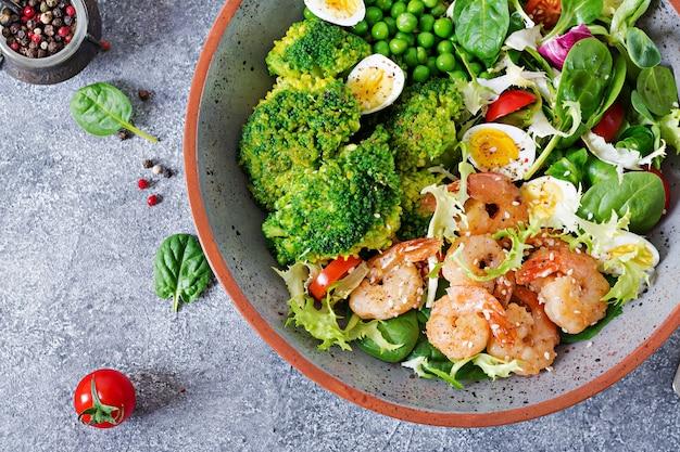 Gezonde saladeplaat. vers zeevruchtenrecept. gegrilde garnalen en verse groentesalade, ei en broccoli. gegrilde garnalen.