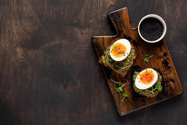 Gezonde sandwich met avocado, eieren en microgreens op toast op een serveerschaal voor het ontbijt. gezonde voeding dieet concept. bovenaanzicht