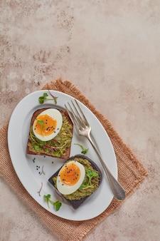 Gezonde sandwich met avocado, eieren en microgreens op toast op een serveerschaal voor het ontbijt. gezonde voeding voedingsconcept. bovenaanzicht.