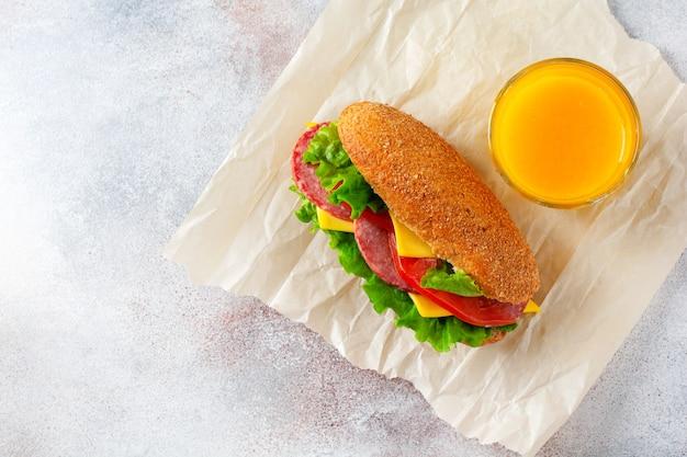Gezonde sandwiches met zemelenbrood, groene sla, kaas, rode tomaat en gesneden salami op perkamentpapier en rustieke houten standaard. ontbijtconcept. bovenaanzicht