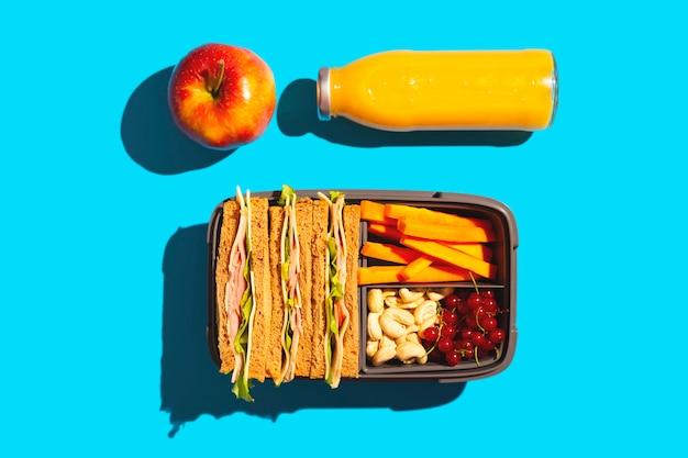Gezonde schoollunch in een handige container op een helderblauwe achtergrond.