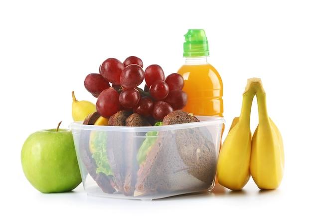 Gezonde schoollunch met sandwich, fruit en sap op wit wordt geïsoleerd