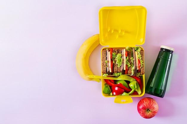 Gezonde schoolmaaltijddoos met rundvleessandwich en verse groenten, fles water en vruchten op roze achtergrond.