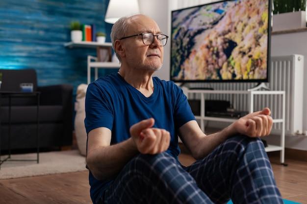 Gezonde senior man zit comfortabel in lotushouding op yogamat met gesloten ogen