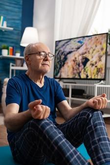 Gezonde senior man zit comfortabel in lotuspositie op yogamat met gesloten ogen werken aan lichaamsmeditatie. kalme gepensioneerde die fitnessoefening uitoefent tijdens training in woonkamer