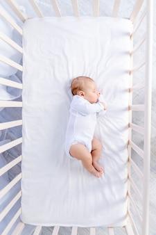 Gezonde slaap van een pasgeboren baby in een kinderbedje in een slaapkamer op een katoenen bed, bovenaanzicht