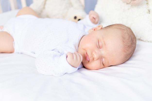 Gezonde slaap van een pasgeboren baby in een wieg in de slaapkamer met een knuffelbeer op een katoenen bed