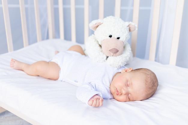 Gezonde slaap van een pasgeboren baby in een wieg in de slaapkamer met een knuffelbeer op een katoenen bed.