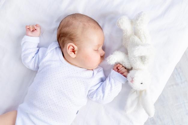 Gezonde slaap van een pasgeboren baby in een wieg in de slaapkamer met een zacht stuk speelgoed in zijn hand op een katoenen bed