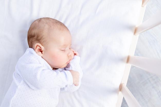 Gezonde slaap van een pasgeboren baby in een wieg in de slaapkamer op een katoenen bed, portret