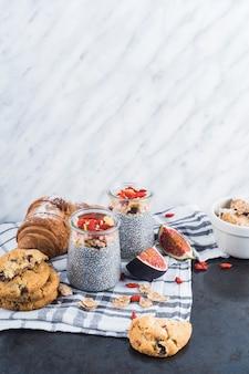 Gezonde smoothie met gesteunde koekjes en croissant op servet tegen marmeren geweven achtergrond