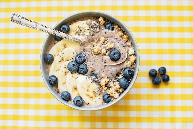 Gezonde smoothiekom met ontbijtbes, gegarneerd met banaan, muesli, bosbessen en chiazaad