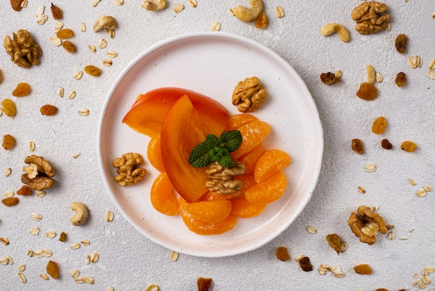Gezonde snack fruit, kaki en mandarijnen met noten op een witte tafel
