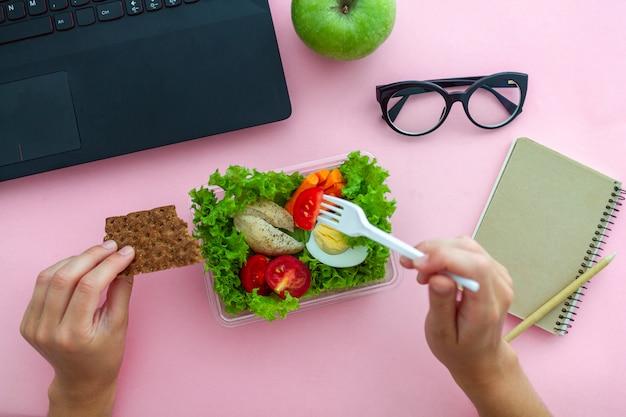 Gezonde snack uit lunchbox op werkplek tijdens de lunchtijd op kantoor. container voedsel op het werk. bovenaanzicht