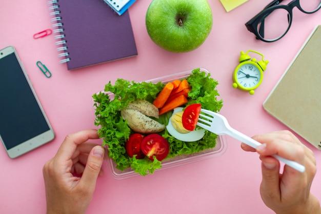 Gezonde snack uit lunchbox op werkplek tijdens lunchpauze op kantoor. eten op het werk. bovenaanzicht