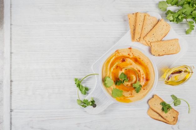 Gezonde snack van knäckebröd met hummus, olijfolie en cillantro op witte houten oppervlak. bovenaanzicht