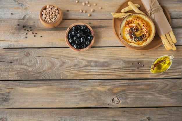 Gezonde snack van knapperig brood met hummus, olijfolie, zwarte olijven en paprika op houten oppervlak. bovenaanzicht met vrije ruimte voor tekst