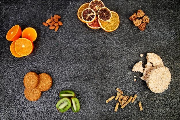 Gezonde snacks - havergranola-reep, rijstcrips, amandel, kiwi, gedroogde sinaasappel