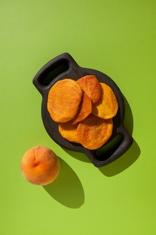 Gezonde snoepjes. gedroogde hele perziken op een houten serveerschaal. verse rijpe perzik ligt vlakbij.