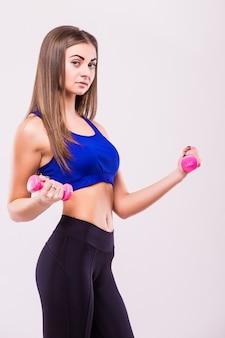 Gezonde spaanse vrouw met halters die geïsoleerd op witte achtergrond uitwerken. fitnessruimte concept