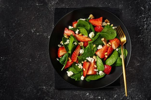 Gezonde spinazie en aardbeisalade op zwarte achtergrond