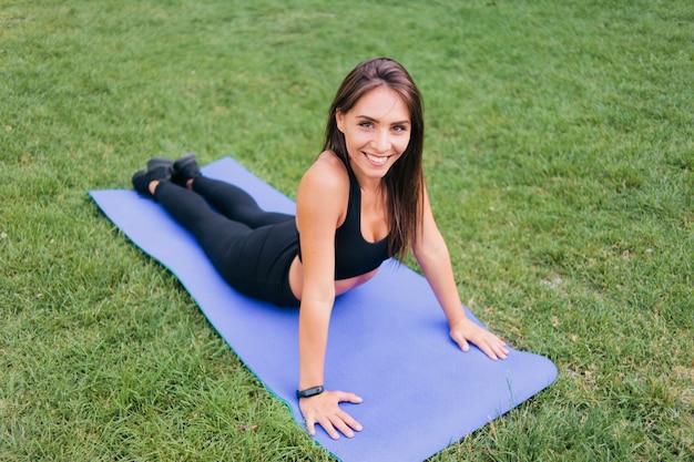 Gezonde sportvrouw in sportkleding die uitrekkende oefening doet die op een mat in het park ligt