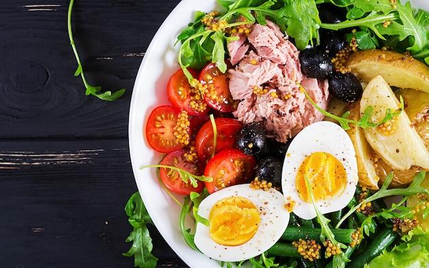 Gezonde stevige salade van tonijn, groene bonen, tomaten, eieren, aardappelen, zwarte olijven close-up in een kom op de tafel.