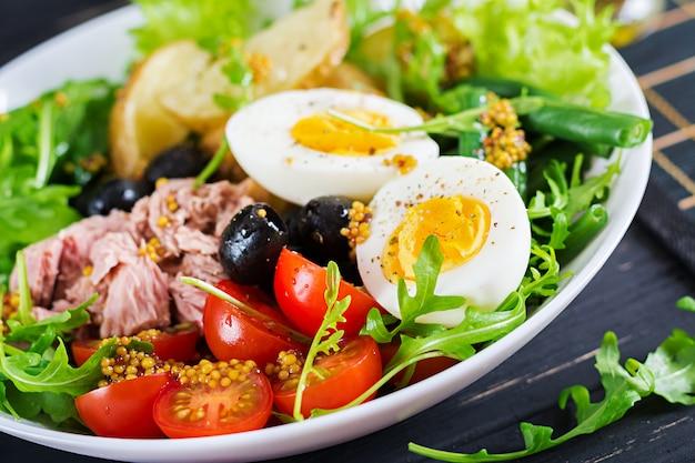 Gezonde stevige salade van tonijn, sperziebonen, tomaten, eieren, aardappelen, zwarte olijven close-up in een kom op tafel. salade nicoise. franse keuken.
