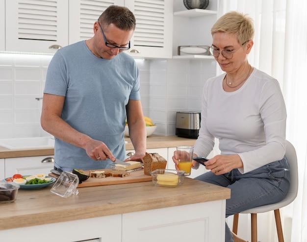 Gezonde stijlvolle senioren paar vrouw kijken naar telefoon man permanent in de buurt van haar en het koken van ontbijt