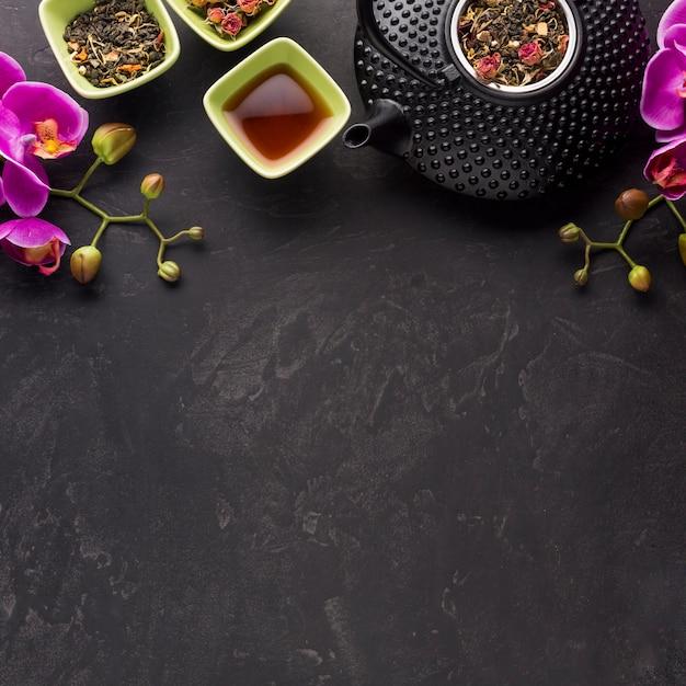 Gezonde thee met droog ingrediënt en roze orchideebloem op zwarte achtergrond