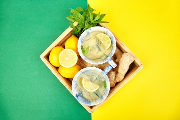Gezonde thee twee kopjes met citroen, gember, munt