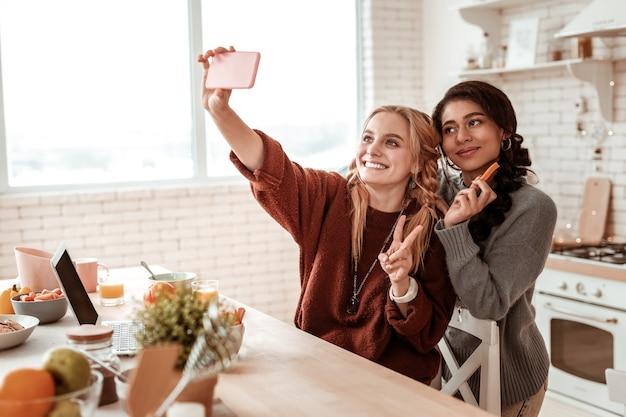 Gezonde tussendoortjes eten. aantrekkelijke positieve dames poseren voor foto terwijl ze een smartphone dragen en twee vingers tonen