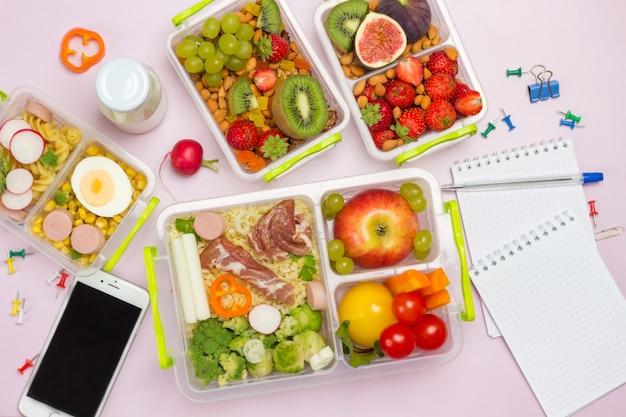 Gezonde uitgebalanceerde lunchboxen met briefpapier en mobiel