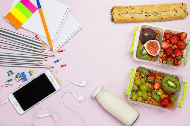 Gezonde uitgebalanceerde lunchboxen met smartphone en briefpapier
