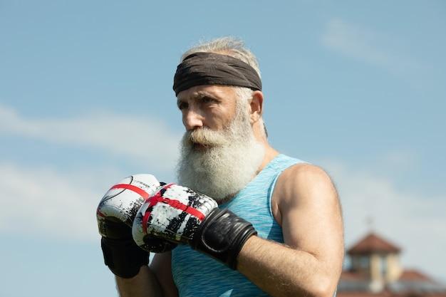 Gezonde vechter bebaarde senior oude man bokshandschoenen.