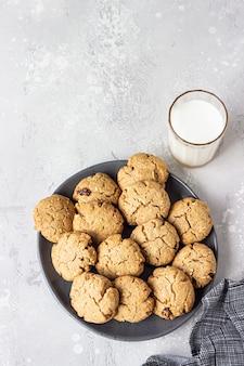 Gezonde vegan cookies met noten en rozijnen op een keramische plaat met melk