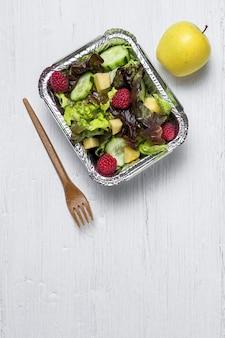 Gezonde veganistische afhaalsalade in aluminium bak of bezorging.