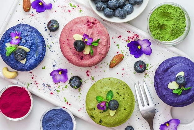 Gezonde veganistische desserts. assortiment rauwe cashew cakes met matcha, acai, bosbessen, munt, noten en bloemen. gluten vrij dieet. bovenaanzicht. plat leggen