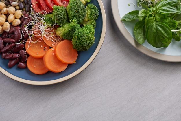 Gezonde veganistische lunchkom, buddha bowl-salade met ingrediënten. kikkererwten, diverse noten en tomaten, broccoli, wortelen.