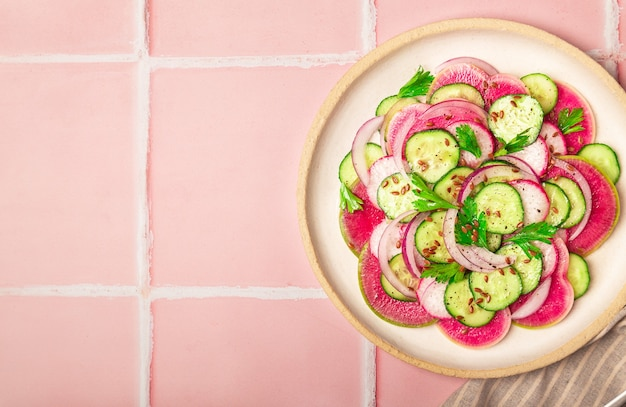 Gezonde veganistische salade met watermeloen, radijskomkommer en rode ui op roze tegelachtergrond bovenaanzicht