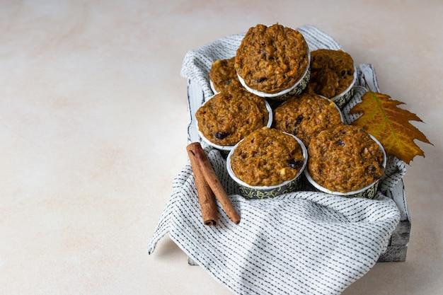 Gezonde veganistische zelfgemaakte wortel- of pompoenmuffins met rozijnen en noten. Premium Foto