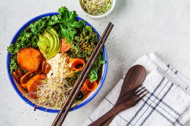 Gezonde veganistlunch in witte kom. boeddha schaal met avocado's