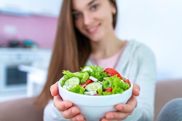 Gezonde veganistvrouw die een kom verse groentesalade houden. evenwichtige biologische voeding en schoon eten