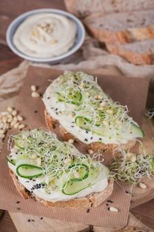 Gezonde vegetarische bruschetta's met brood, microgreens, hummus, komkommers en pijnboompitten