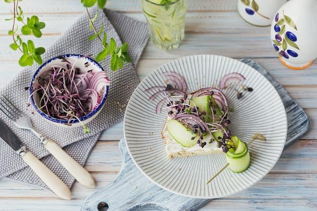 Gezonde vegetarische bruschetta's met brood, microgroenten, kaas, komkommers en rode ui