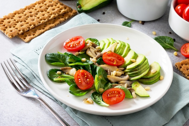 Gezonde vegetarische lunchkom avocado-champignons, kerstomaatjes, pijnboompitten, spinazie en dressing met vinaigrette saus