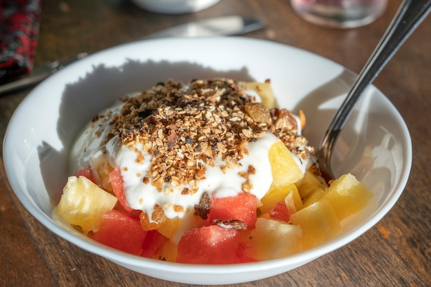 Gezonde vegetarische ontbijtkom met yoghurt, muesli granen, watermeloen en ananas