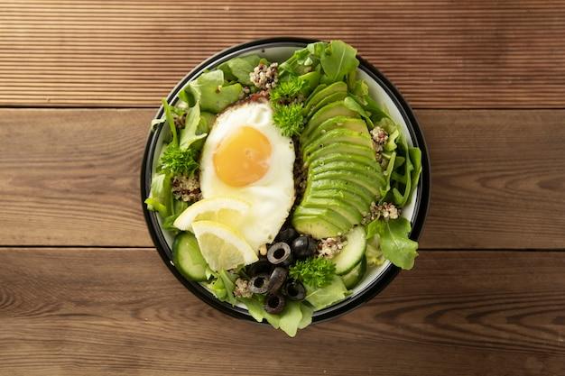 Gezonde vegetarische ontbijtkom. quinoa, avocado, ei, groene salade, zwarte olijven over houten achtergrond. energieopwekking, schoon eten, dieetvoeding concept