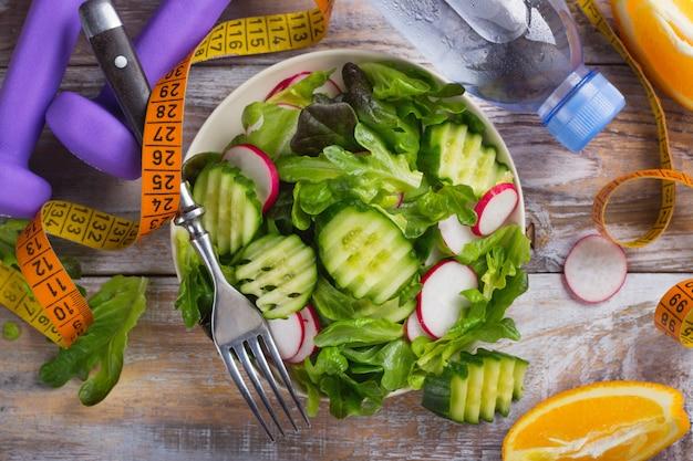 Gezonde vegetarische salade, halters en fles water op houten tafel